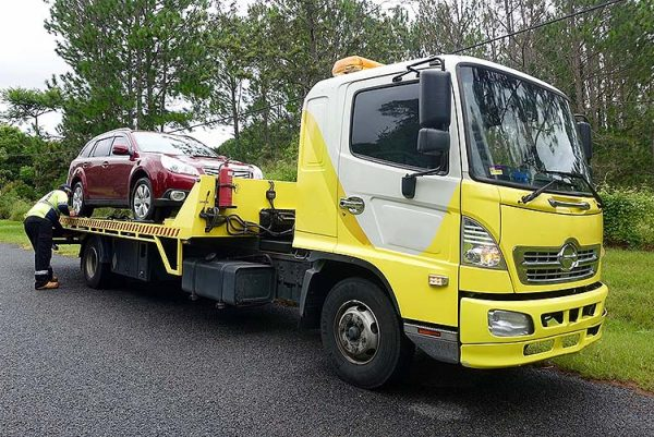 Yellow Recovery Truck towing a red car